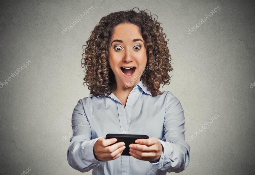 Shocked girl looking at phone bad news wow face expression