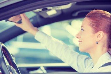 woman driver looking adjusting rear view car mirror