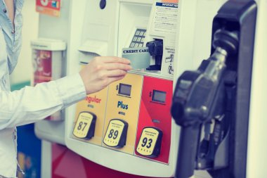 Woman hand swiping credit card at gas pump station