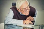 Fotografie Älterer alter Mann sitzt mit Laptop am Tisch