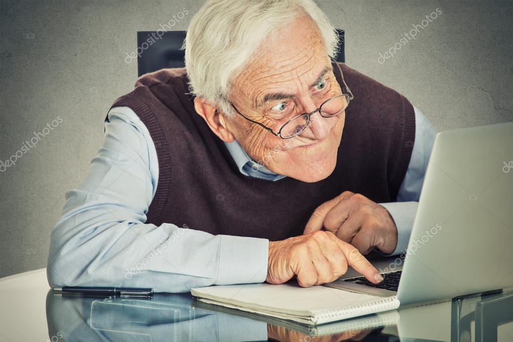 Elderly old man using laptop computer sitting at table