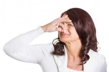 woman covers her nose disgusted something stinks