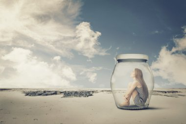 young woman sitting in a jar in the desert. Loneliness outlier concept
