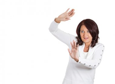 Scared woman trying to protect herself arms raised up in defense