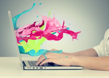 Hands on keyboard with colorful splashes out of monitor