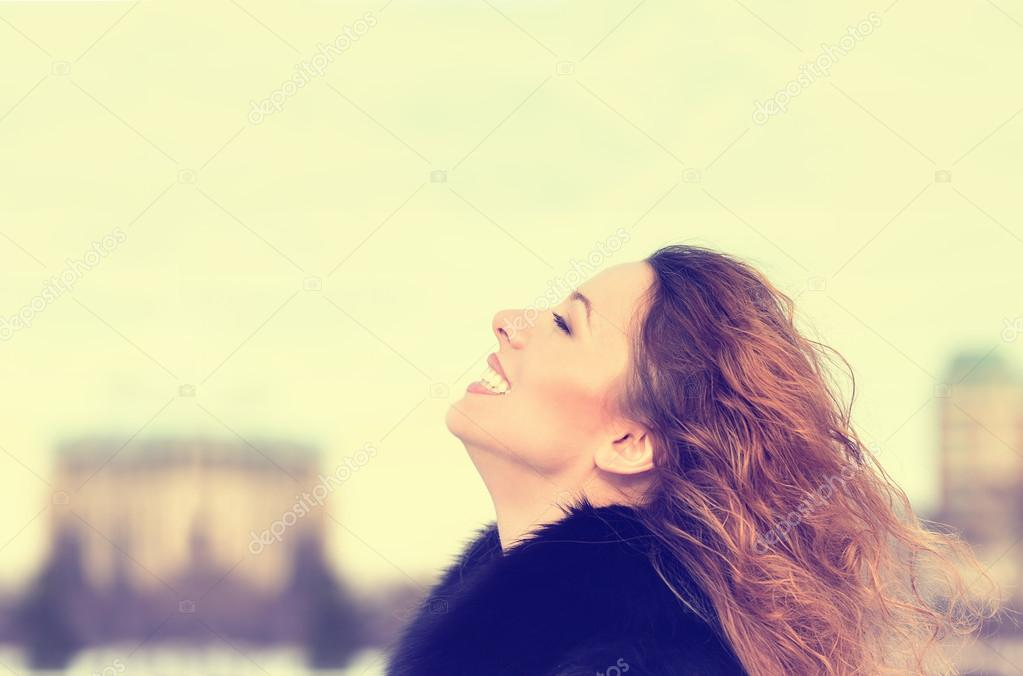 Woman smiling looking up to blue sky taking deep breath