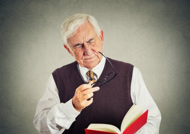 elderly man holding book, glasses having eyesight problems