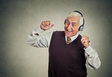 elderly man with headphones listening to radio enjoying music