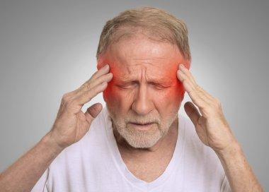 senior man suffering from headache hands on head
