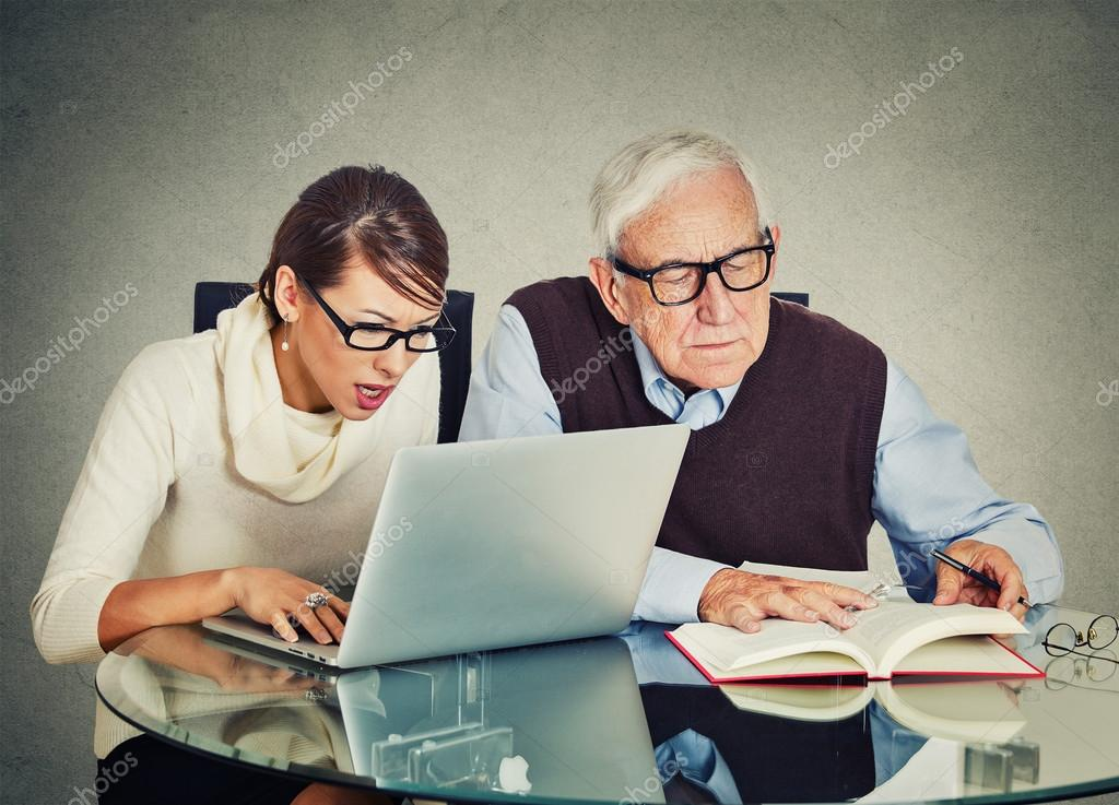Mulher trabalhando no laptop e velho vov leitura do livro portrait young woman working on laptop and older senior mature grandpa man reading from book on table isolated gray wall background fandeluxe