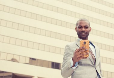 happy cheerful man excited by what he sees on cell phone