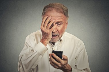 Stressed man holding cellphone shocked with message received