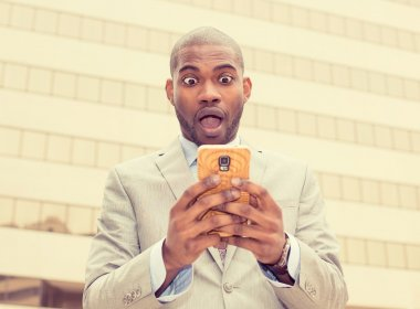 Closeup portrait anxious young business man looking at phone seeing bad news or photos with disgusting emotion on his face isolated outside city background. Human emotion, reaction, expression stock vector
