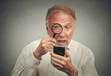 Curious. Senior man looking through magnifying glass at smartphone