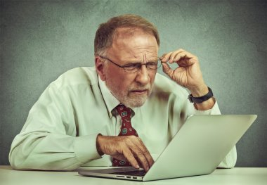 elderly man with glasses confused with laptop software