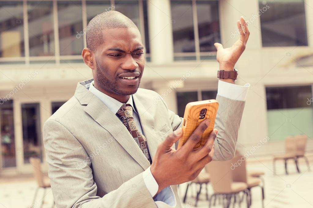 Closeup unhappy young man in suit talking texting on cellphone outdoors