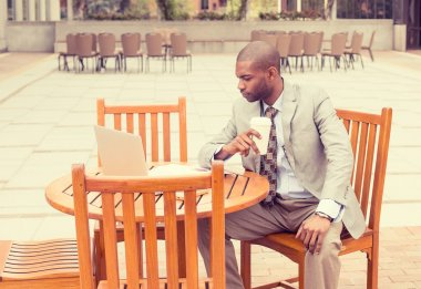 businessman working outdoors reading documents drinking coffee