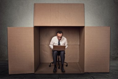 man working on laptop sitting on chair inside carton box