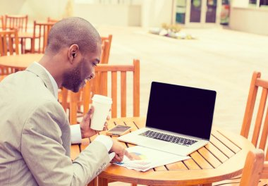 man working outdoors reading documents using laptop