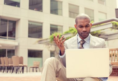 man sitting outside office looking at laptop frustrated about computer crash