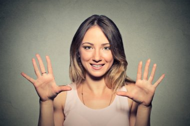 happy young woman making five times sign gesture with hands
