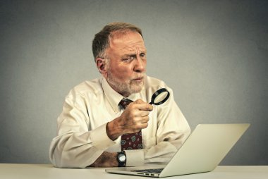 senior man working looking through magnifying glass at laptop screen