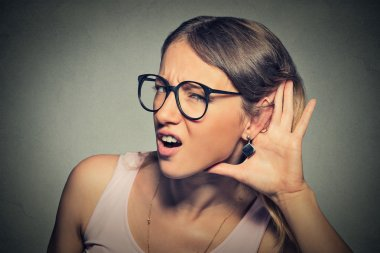 Nosy woman hand to ear gesture or hard to hear concept
