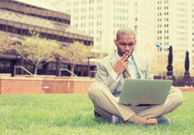 business man sitting outside corporate office working on computer