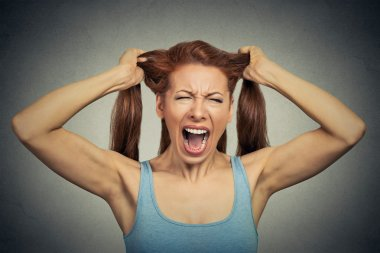 Portrait of a very angry woman screaming acting out