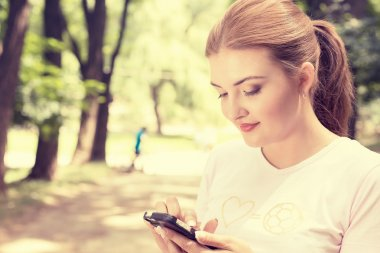 Closeup portrait, happy, cheerful, young woman excited by what she sees on cell phone sitting outdoors in park. Facial expression, reaction. Smiling girl sending text message from her mobile stock vector
