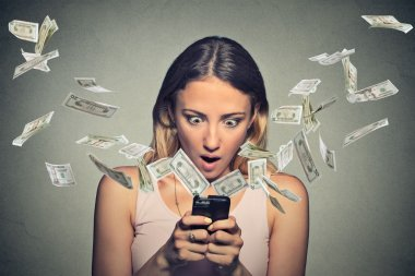 Shocked woman using smartphone dollar bills flying away from screen