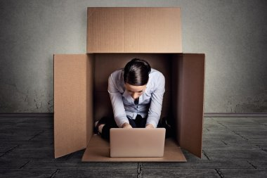 businesswoman sitting in carton box working on laptop computer
