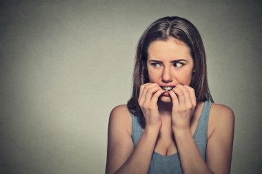 unsure hesitant nervous woman biting her fingernails