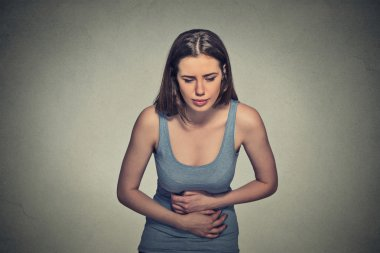 woman hands on stomach having bad aches pain