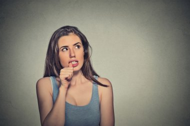 nervous looking young woman biting her fingernails