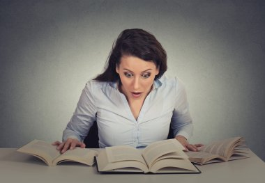 shocked woman sitting at desk with many opened books reading