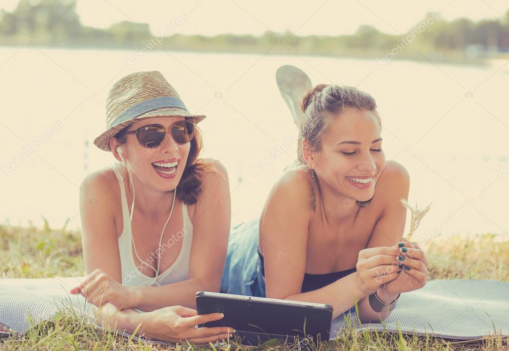 Two funny happy young women friends enjoying summer day outdoors