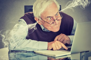 Frustrated elderly old man using laptop computer sitting at table
