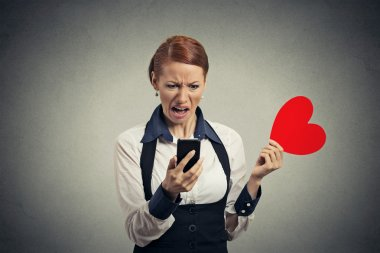 displeased young woman reading news on smart phone throwing away red heart
