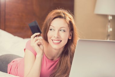 woman with laptop shopping on line holding showing credit card