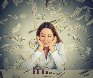woman sitting at table with growing stack of coins under a money rain