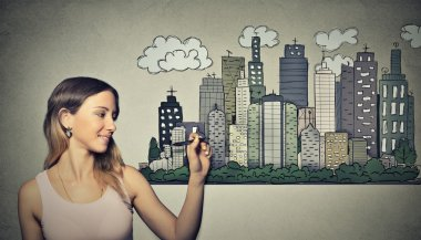 Woman drawing city skyline. Real estate development