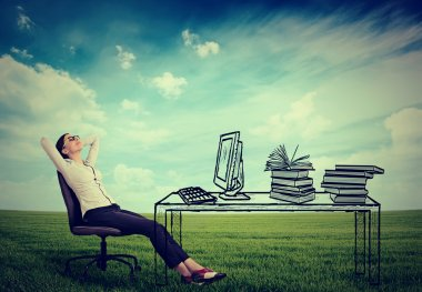 young businesswoman relaxing sitting in the office in the middle of a green meadow