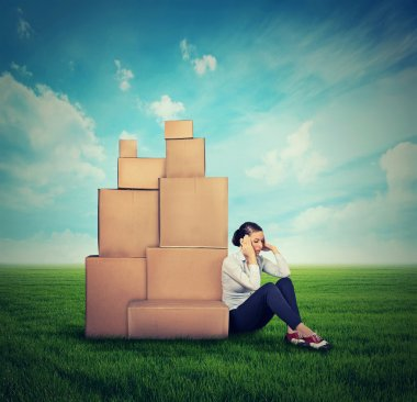 young stressed woman sitting on the ground green grass with many boxes