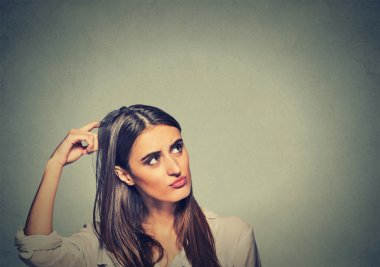 Contused thinking woman bewildered scratching her head seeks a solution