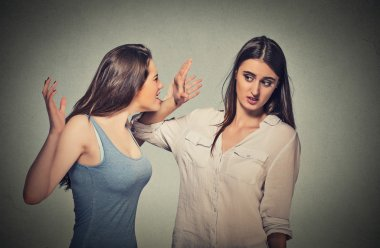 Girl patronizing screaming at shy timid woman