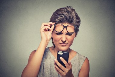 headshot young woman with glasses having trouble seeing cell phone