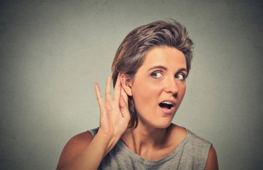surprised young nosy woman hand to ear gesture secretly listening
