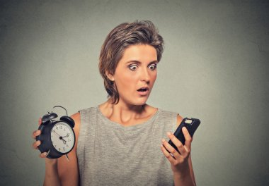Young woman with mobile phone and alarm clock stressed running late