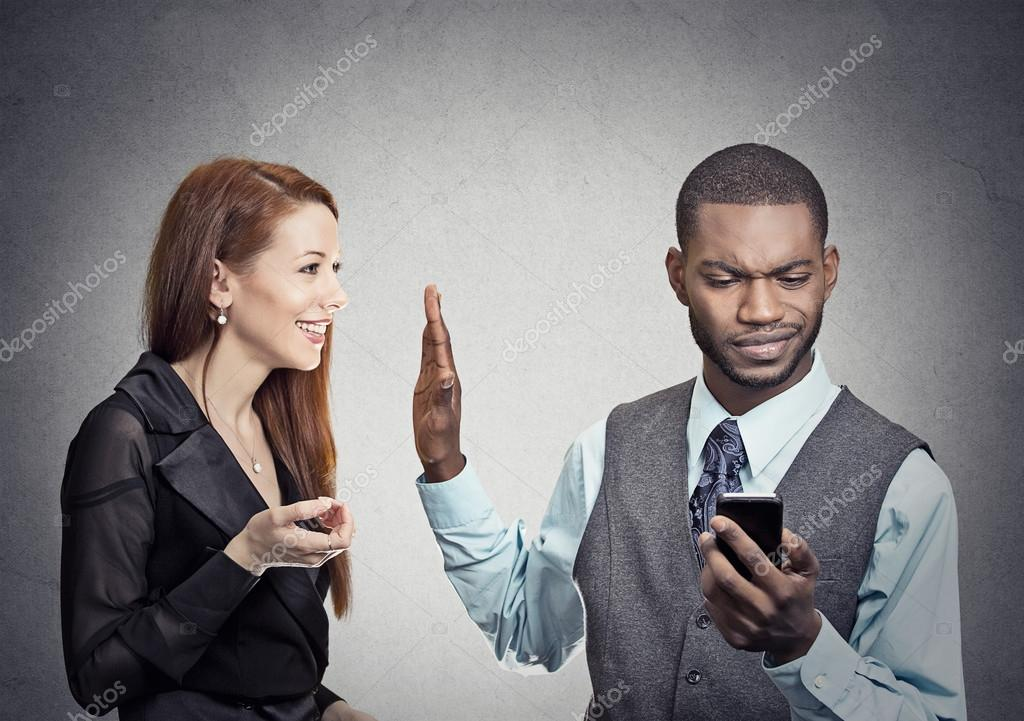 Woman being ignored stopped by young handsome man looking at smartphone